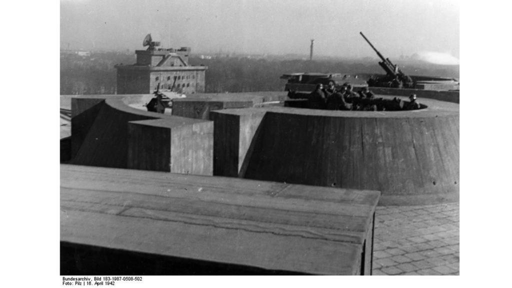 Auf dem Dach des Zoo-Flakturms ist ein Entfernungsmesser (vorne) und ein Flak-Geschütz (hinten) zu sehen. Im Hintergrund steht der Leitturm.